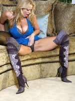 Kelly was wearing a short blue dress and snakeskin thigh high boots when she fingers her hole.