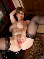 Horny Anilos pinches her big mature tits and stroking her pussy with a red toy on the couch