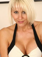 Blonde MILF Jan poses before slipping a big glass dildo inside of her