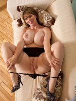 Cougar babe pinches her huge mature tits on the couch and slides off her thongs to exposed her pussy
