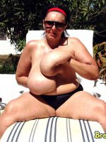 Busty mature taking sunbath