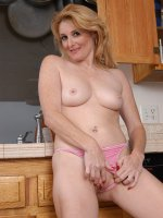 Sweet MILF spreads her pussy lips wide in the kitchen