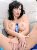 Naughty Alia Janine rubs her toy between her massive mature tits before she uses it outdoors