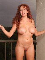 Busty redheaded MILF spreads wide on the balcony